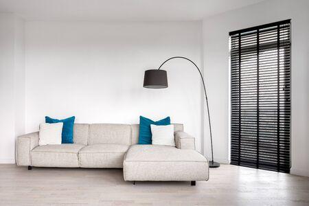 Living room interior with big corner sofa and balcony door
