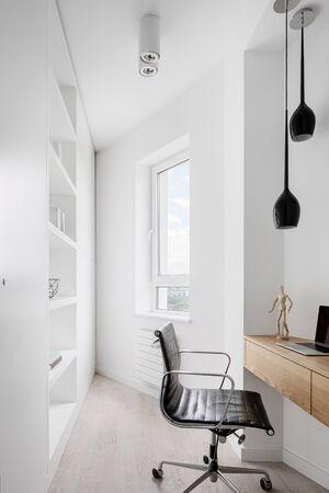 Simple corner home office interior in white with wooden desk Archivio Fotografico