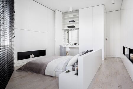 Elegant bedroom interior in white with big bed, window and dressing table built-in wardrobe