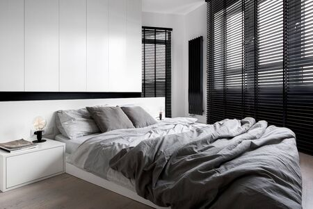 Designed bedroom with window wall, long black window blinds and big bed