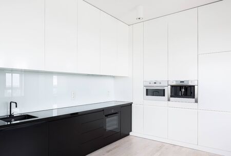 Elegant black and white elegant kitchen with many cupboards and build in kitchen equipment