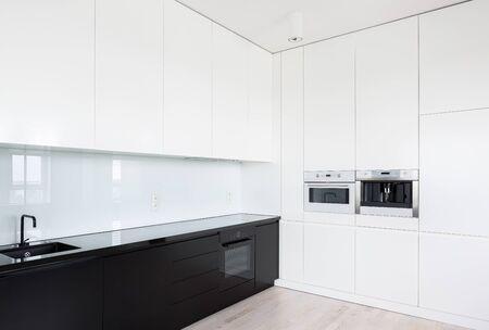 Elegante schwarz-weiße elegante Küche mit vielen Schränken und eingebauter Küchenausstattung Standard-Bild