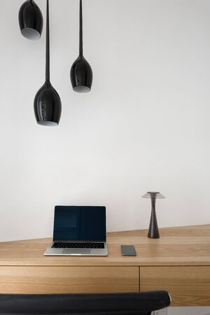Black ceiling lamps and small black lamp with modern computer and phone on simple wooden desk Reklamní fotografie
