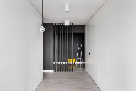 Elegant corridor interior with many white wardrobes and black area with seat and clothes hanger