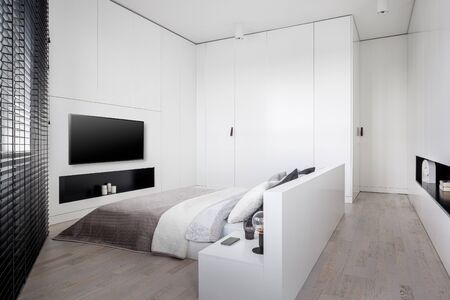 Elegant white bedroom with big bed, many wardrobes and lockers and big tv