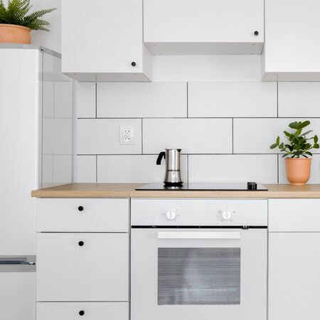 Contemporary kitchen with white tiles, wooden worktop and induction hob Stock fotó