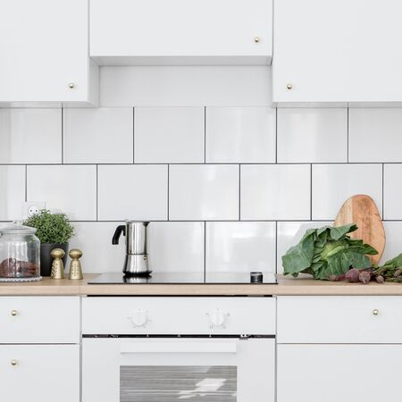 White kitchen with classic wall tiles, simple cupboards and induction hob with oven