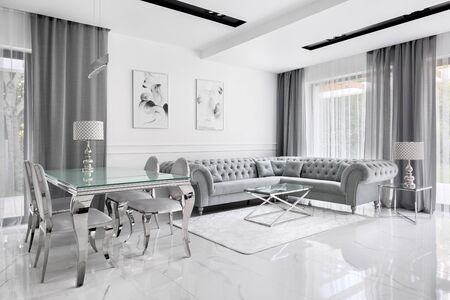 Charming and luxury living room in gray and white with glass table and glamour style corner sofa Archivio Fotografico