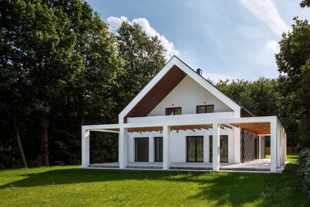 Amazing and new white house with wooden decorations and green lawn