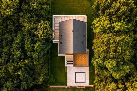 Aerial view of modern designed house with garden surrounded by forest during sunset