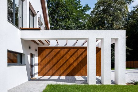 Elegant house with modern designed entrance with wooden elevation and white pillars