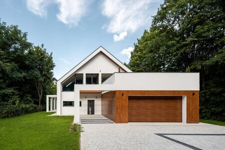 New white house with cobblestone driveway and garage with wooden elevation