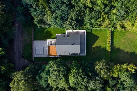 Aerial view of modern house with green lawn surrounded by forest