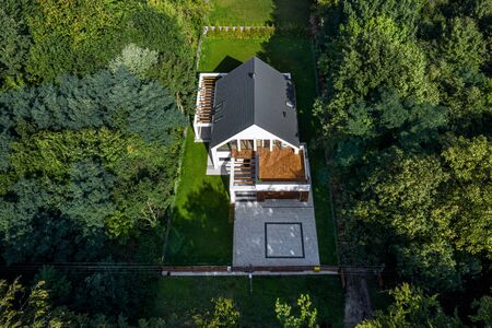 Aerial view of designed modern house with green garden and cobblestone driveway