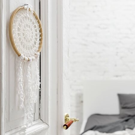 Interior with white brick wall and knitted decoration hanging on the bedroom door Imagens