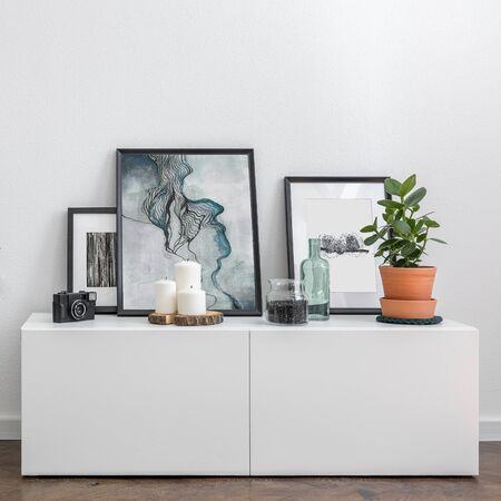 Home interior with simple white sideboard and artistic decorative accessories