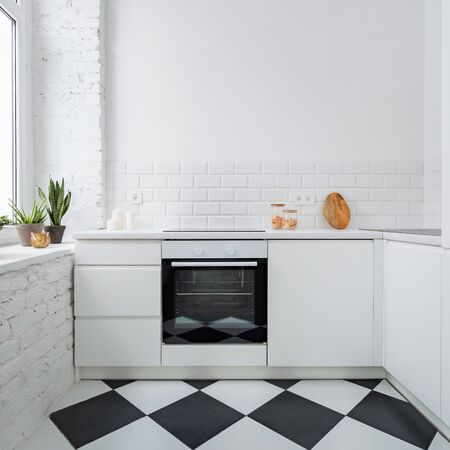 Narrow kitchen with white brick wall and chess mosaic tiles on the floor