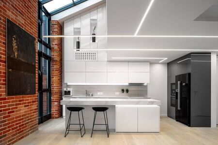 Elegant and modern kitchen in white with brick wall and big windows Stock Photo