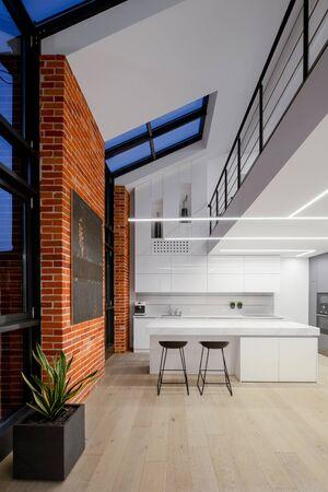 Appartamento in stile loft con soppalco, muri in mattoni e grandi finestre