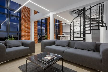 Loft style apartment with living room open to kitchen, spiral stairs, brick walls and big windows