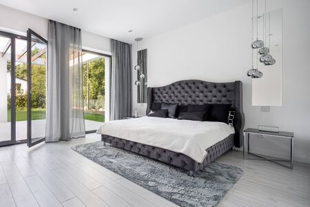 Glamour style gray bedroom interior with quilted headboard of the bed Stock fotó