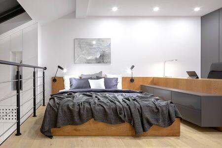 Moderna camera soppalcata con letto in legno e lunga scrivania in legno