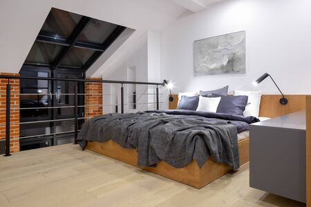 Modern bedroom on mezzanine in loft style apartment with big window and brick wall
