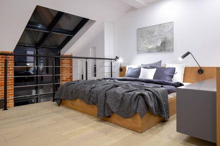Modern bedroom on mezzanine in loft style apartment with big window and brick wall Archivio Fotografico