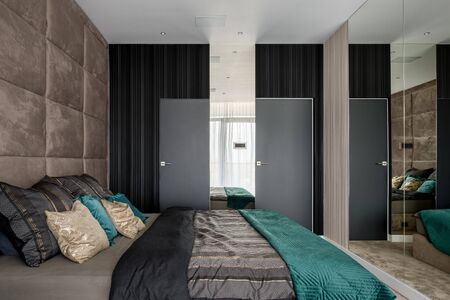 Elegant bedroom with mirrored and upholstered walls and vinyl wallpapers