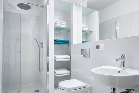 Baño blanco de diseño simple con ducha y lavabo clásico. Foto de archivo