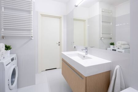 Simple bathroom with washing machine and long washbasin on wooden chest with drawers Stockfoto