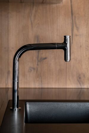 Modern chrome faucet and black sink in kitchen with wooden walls Foto de archivo