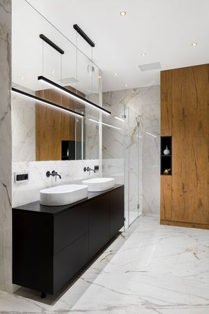 Elegant bathroom in white marble tiles on floor and walls and with black chest of drawers under two washbasins