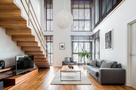 Two-floor apartment with spacious living room with wooden stairs, hardwood floor and many, big windows Stockfoto