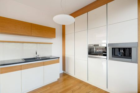Modern white gloss kitchen with stylish wooden floor, cupboards and wall