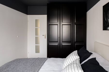 Simple bedroom with big bed, black wardrobe, white walls and black ceiling