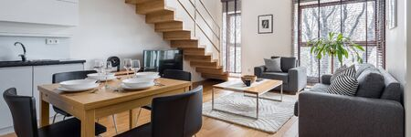 Panorama of stylish two-floor apartment with kitchen and dining area open to living room and wooden stairs to higher floor