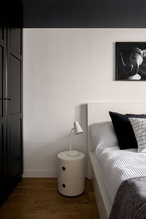 Black and white bedroom interior with big black wardrobe and simple white lamp on white nightstand