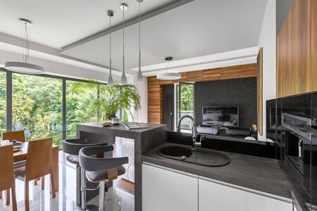 Elegant kitchen open to living room and dining area in apartment with window wall