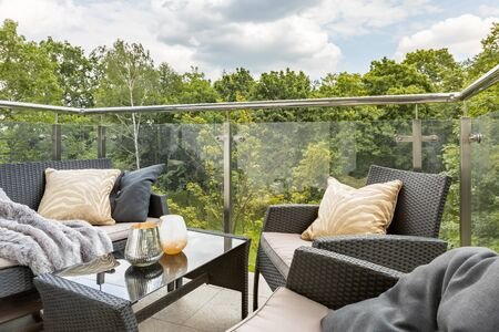 Stylish balcony with elegant rattan furniture and glass walls and green forest view
