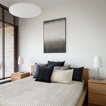 Big and comfortable bed in bright bedroom and two wooden nightstands with lamps