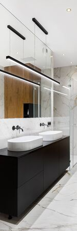 Vertical panorama of elegant bathroom with black chest of drawers under two washbasins and led lights Foto de archivo