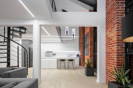 Open plan loft style apartment in white, with brick walls, pillars, mezzanine floor and spiral stairs