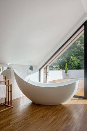 Luxury bathtub in elegant bathroom with big window and balcony