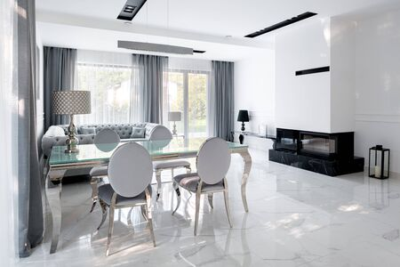 Glamour style living room in white and silver and dark marble fireplace and white marble floor