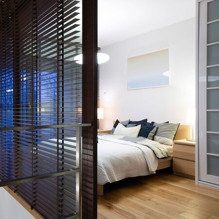 Stylish bedroom with wooden floor and window walls and lights on, evening