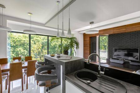 Elegancka kuchnia z szarymi blatami i drewnianym stołem jadalnym otwarta na salon z dużym oknem i telewizorem