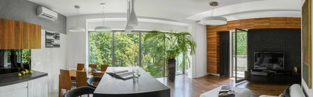 Panorama of elegant apartment with big window wall and with kitchen open to living room