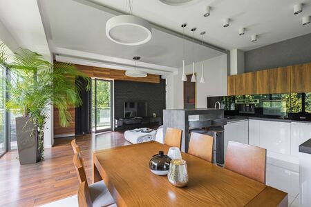 Wooden dining table in open plan apartment where kitchen is connected with living room Standard-Bild