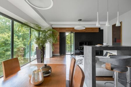Wooden dining table with chairs in elegant living room with window wall and balcony